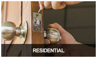 Image of a locksmith installing a residential lock on a front door.