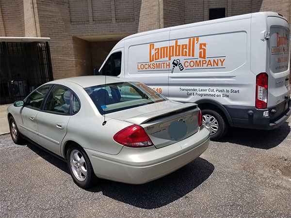 image of our locksmith van next to a customer's Ford Taurus